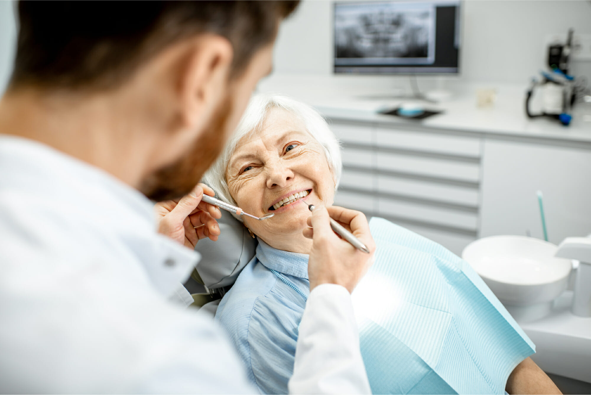older woman smiling at dentist