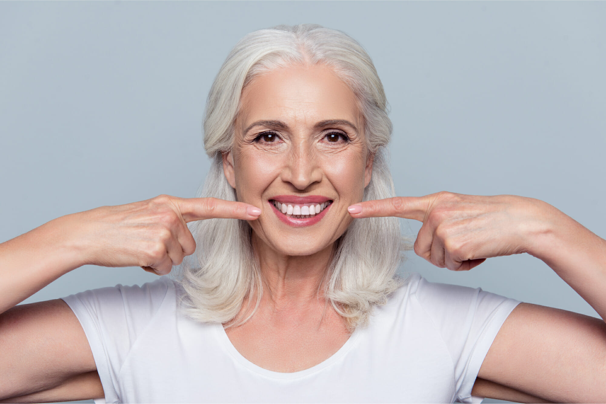 older woman pointing at her smile